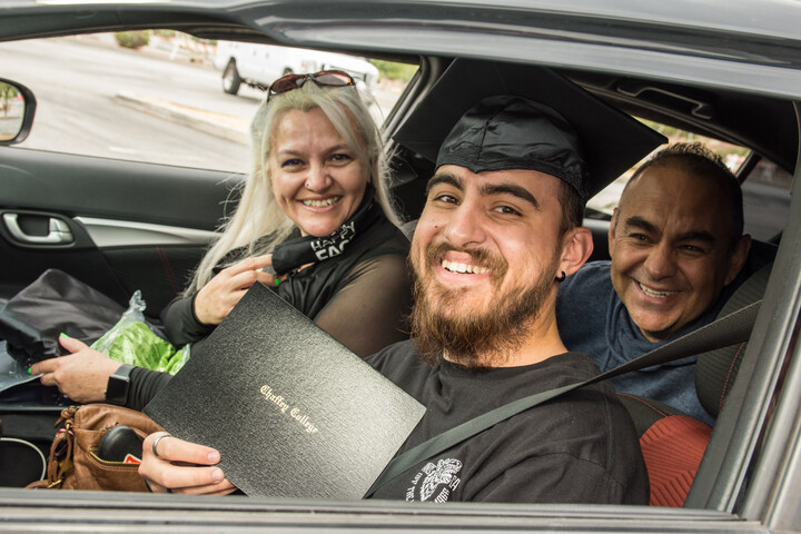 Graduate student in a car and showing his diploma