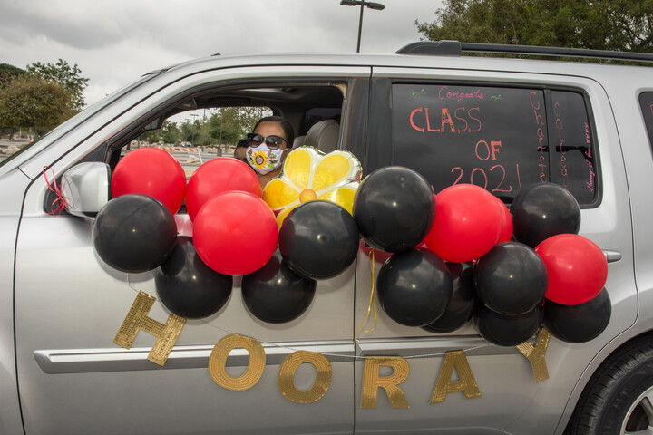 Graduate student driving a vehicle decorated with red, yellow and black balloons.