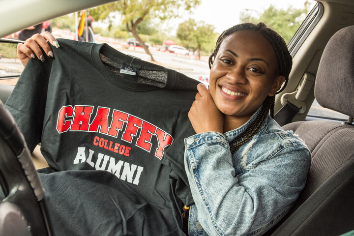 Graduate student in her car and showing a Chaffey College Alumni T-shirt
