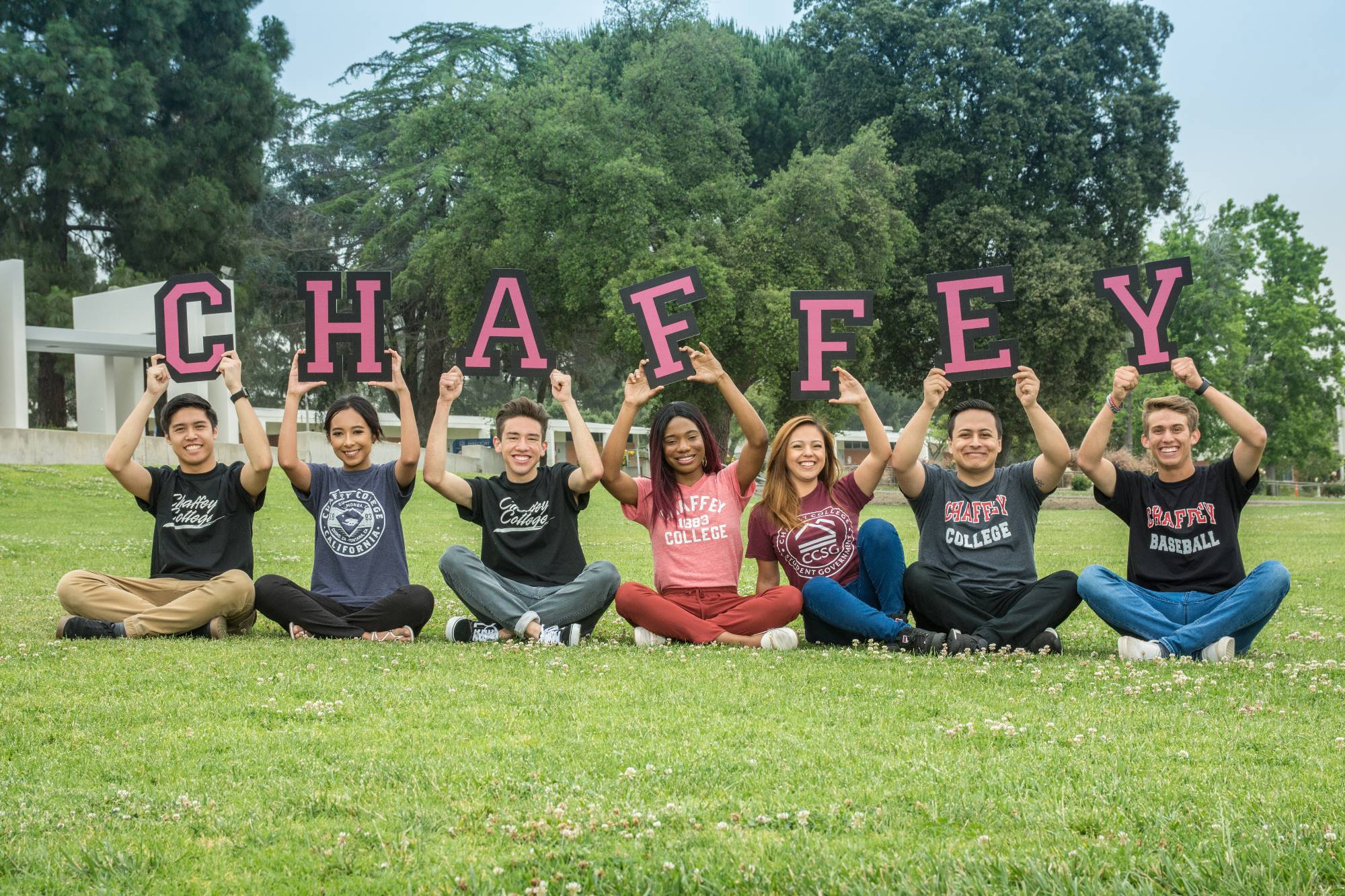 "Students hold up the letters ""Chaffey"" as they sit on the grass on campus."