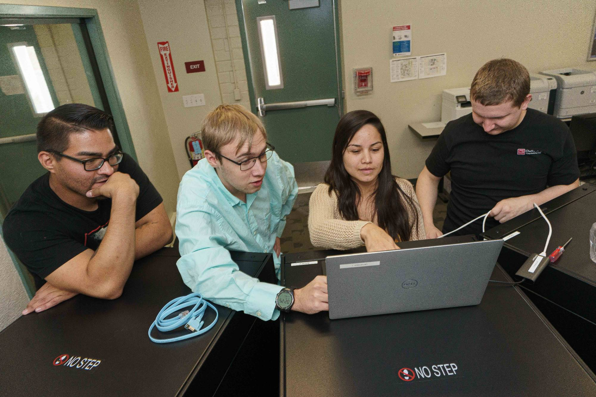 Cybersecurity students examine a laptop during a class.