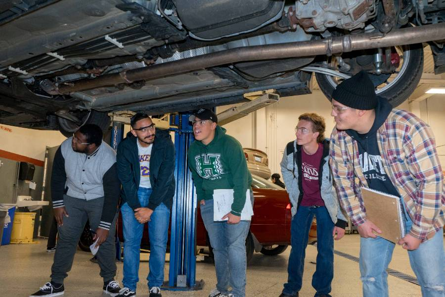 Students in the auto technology program examine the underside of a vehicle.