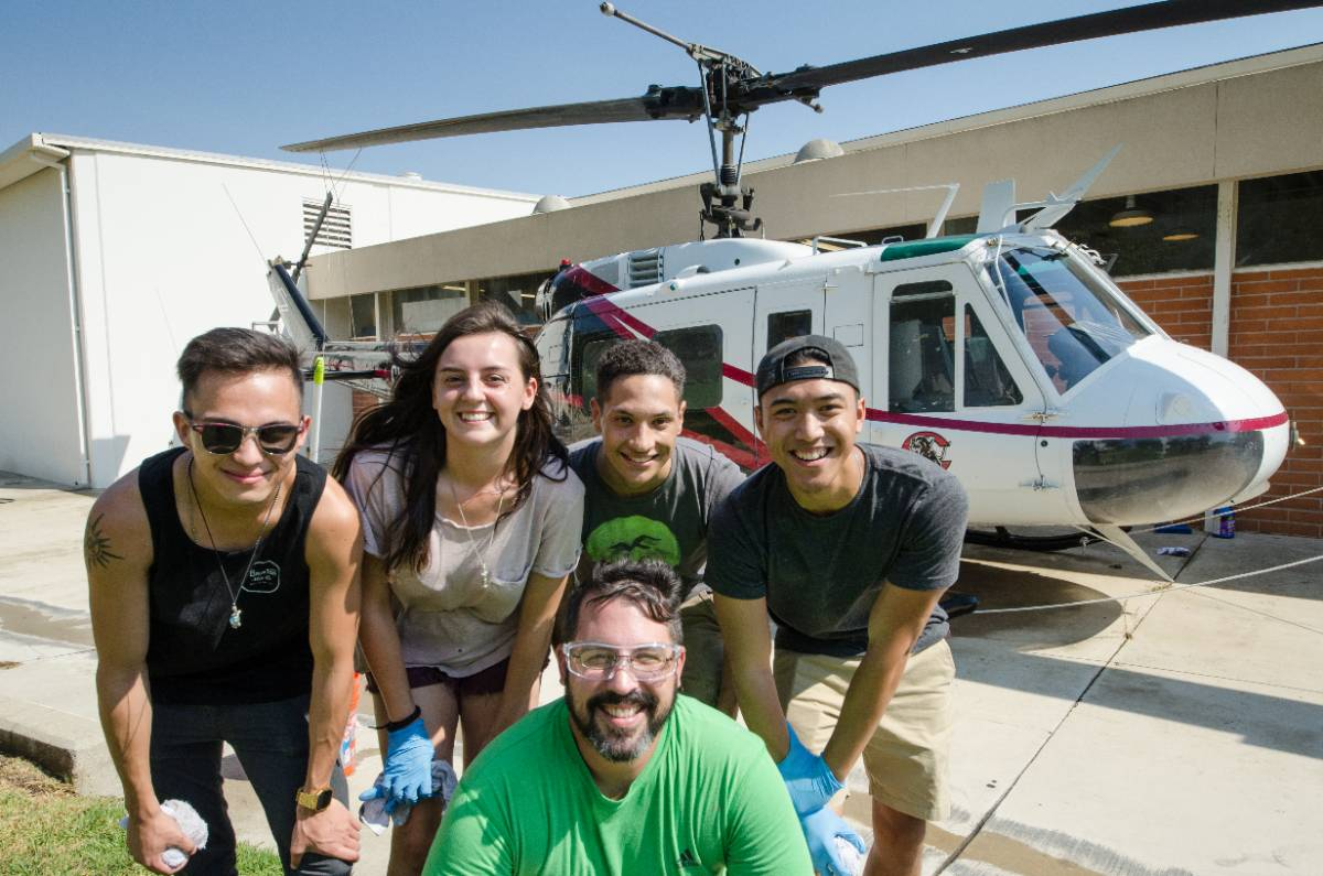 Students pose in front of the Chaffey College helicopter at the aeronautics building.