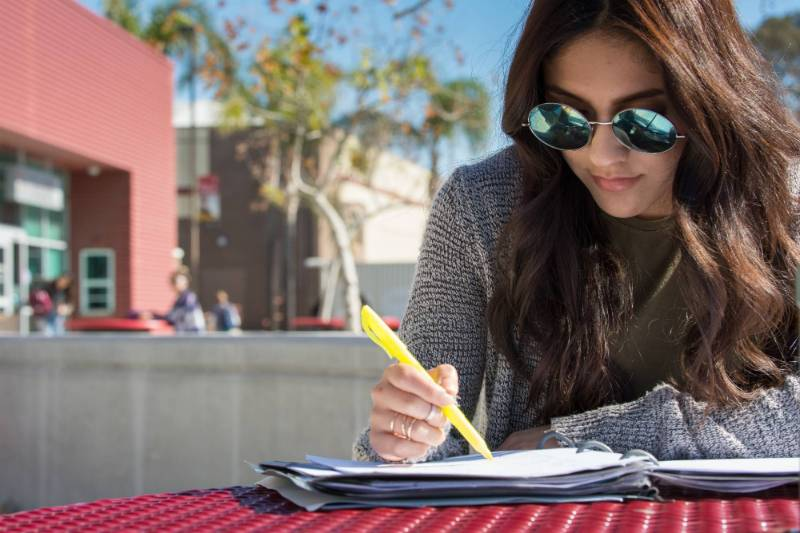 A student wearing sunglasses highlights some notes at the Fontana campus.